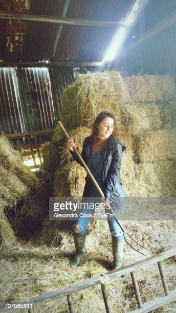 Smiling Woman Holding Garden Fork While Standing At Barn