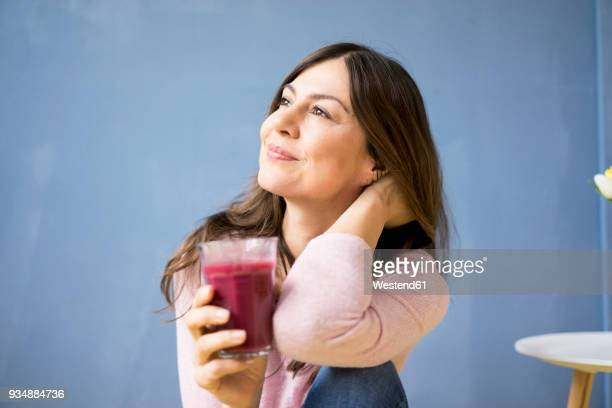 smiling woman holding glass of juice - juice drink stock photos and pictures
