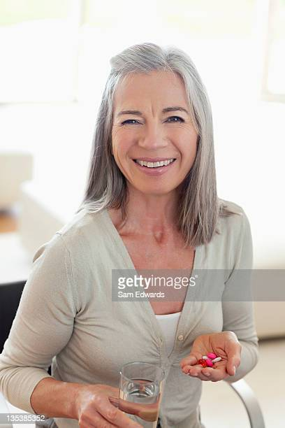 Smiling woman holding glass of water and pills