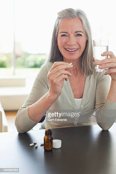 Smiling woman holding glass of water and taking pills