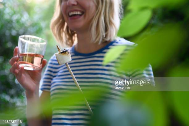 smiling woman holding glass of wine and toasted marshmallow - montclair stockfoto's en -beelden