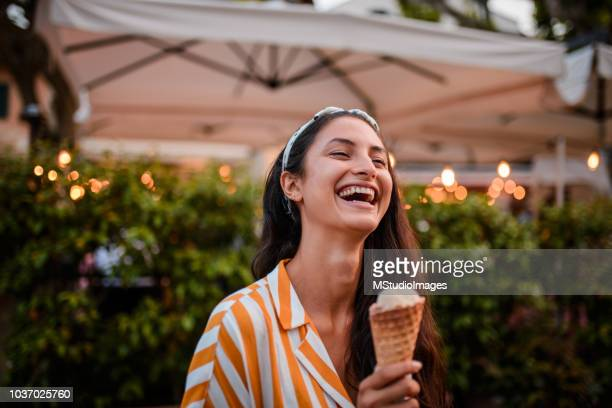 smiling woman holding icecream. - gelato italiano foto e immagini stock