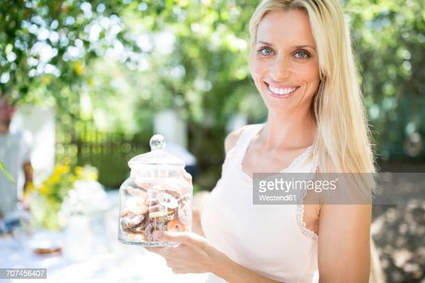 Smiling woman holding jar with cookies outdoors