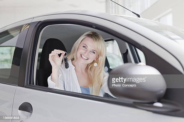Smiling woman holding keys to new car