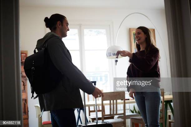 Smiling woman holding keys while talking to man in apartment on sunny day