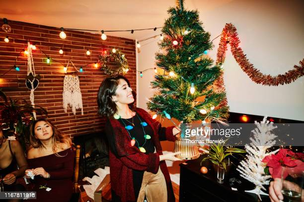 Smiling woman holding miniature Christmas tree during holiday party with friends