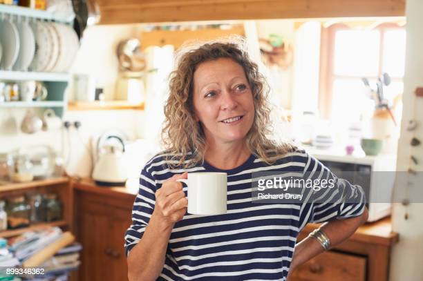 Smiling woman holding mug of tea