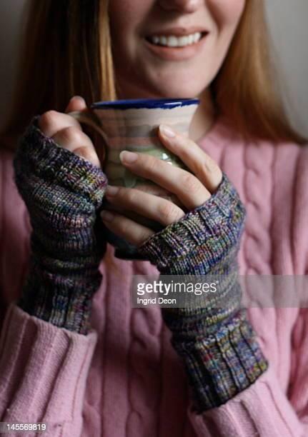 smiling woman holding mug - 指なし手袋 ストックフォトと画像