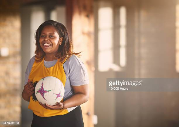 Smiling woman holding netball in gym.