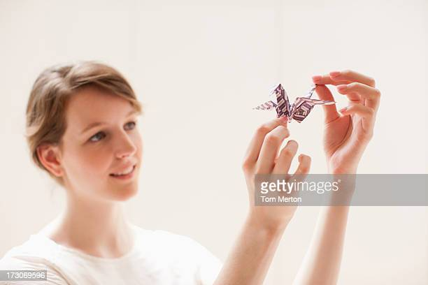 Smiling woman holding origami bird