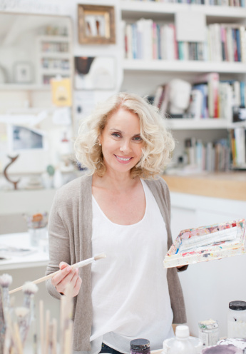 Smiling woman holding paintbrush and palette in art studio - gettyimageskorea