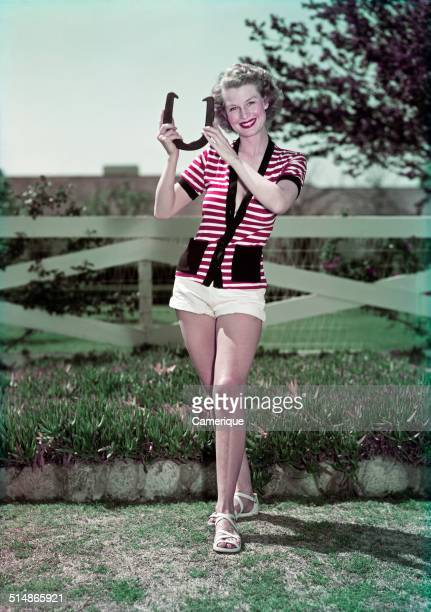 Smiling woman holding pitching horseshoe fence in background Los Angeles California 1949