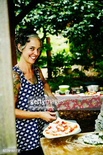Smiling woman holding pizza peel in backyard