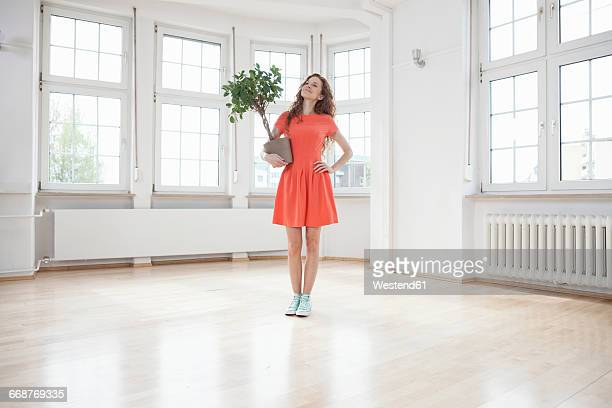 Smiling woman holding plant in empty apartment