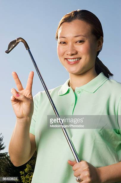 Smiling woman holding putter and two fingers out, close-up