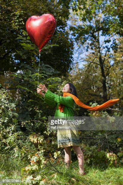 Smiling woman holding red heart shape balloon while standing on field against trees at park