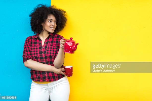 Smiling woman holding red teapot and cup on colorful background