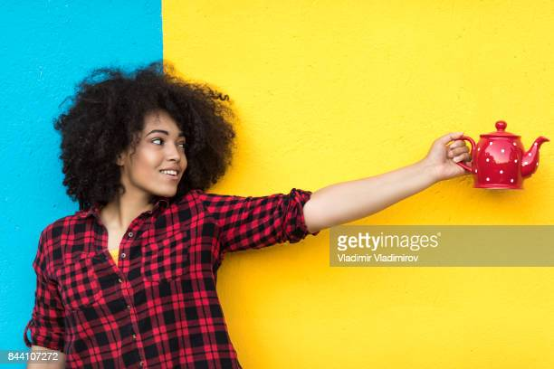 smiling woman holding red teapot on colorful background - plaid shirt stock pictures, royalty-free photos & images