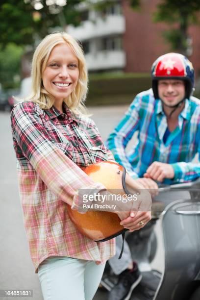Lächelnde Frau hält einen scooter-Helm