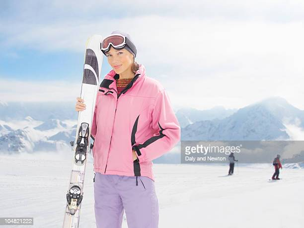 smiling woman holding skis on snowy mountain - skiing stock pictures, royalty-free photos & images