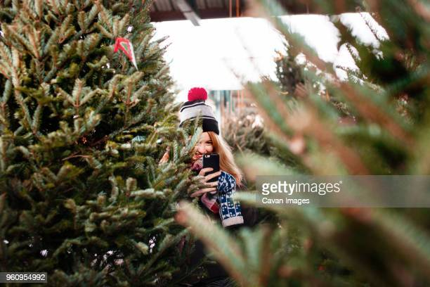 Smiling woman holding smart phone and standing amidst Christmas trees