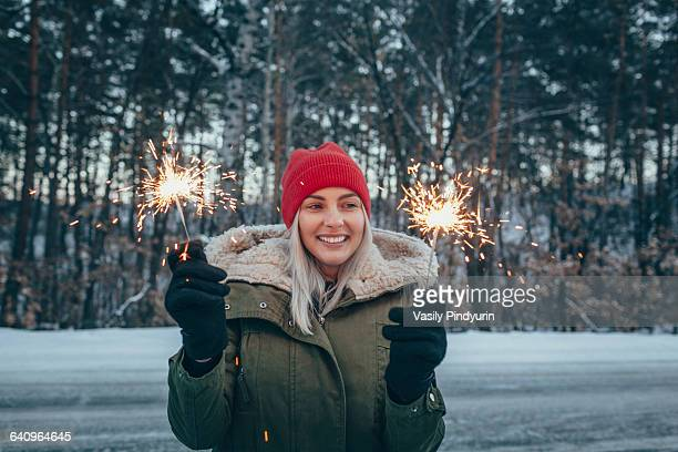 Smiling woman holding sparklers during winter