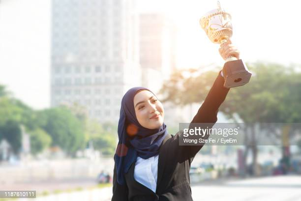 smiling woman holding trophy while standing in city - award stock pictures, royalty-free photos & images