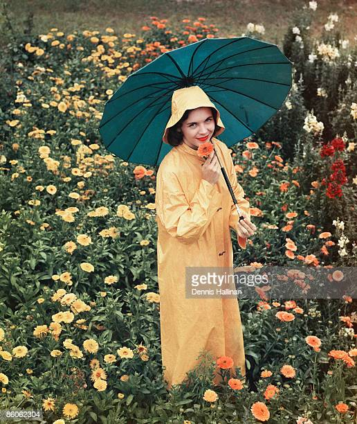 smiling woman holding umbrella in field of flowers - vintage raincoat stock photos and pictures