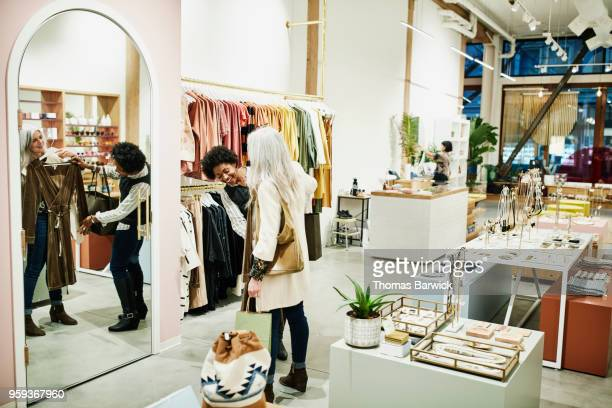 smiling woman holding up dress for friend while shopping together in clothing boutique - older women in short skirts stock pictures, royalty-free photos & images