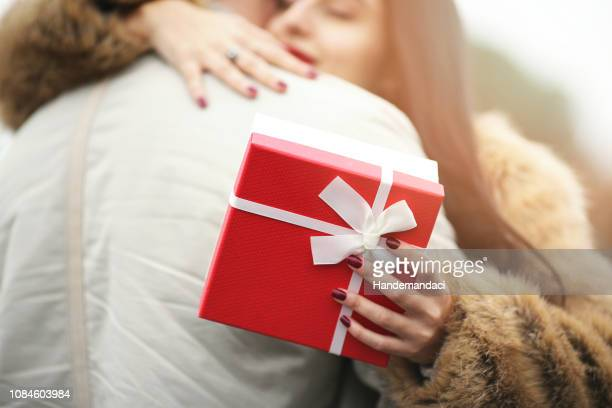 smiling woman holding valentine's day gift and hugging man - valentine's day holiday stock pictures, royalty-free photos & images