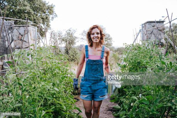 smiling woman holding watering can while standing amidst plants in vegetable garden - カバーオール ストックフォトと画像