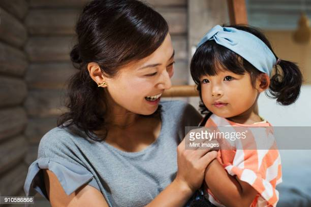 smiling woman holding young girl with black pigtails wearing blue hairband. - only japanese stock pictures, royalty-free photos & images