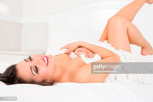 Smiling woman hugging blanket laying on bed