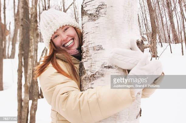 smiling woman hugging tree - tree hugging stock pictures, royalty-free photos & images