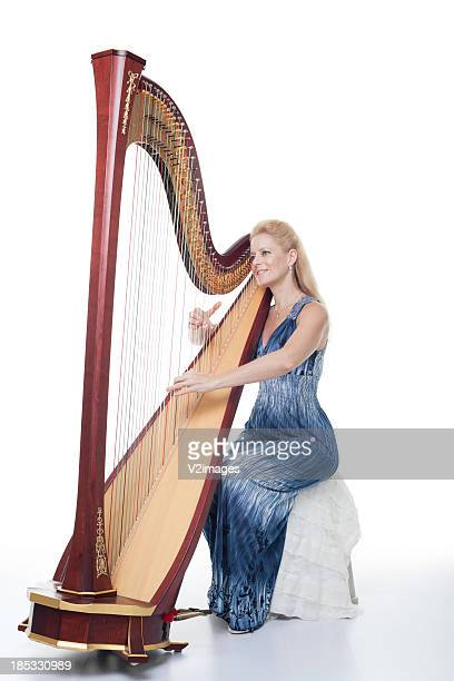 Smiling woman in a blue dress playing the harp