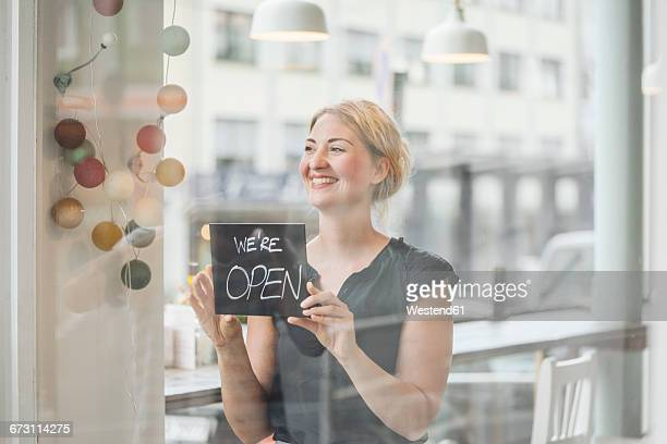 smiling woman in a cafe attaching open sign to glass pane - 創始者 ストックフォトと画像