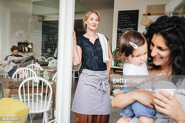 Smiling woman in a cafe with customers