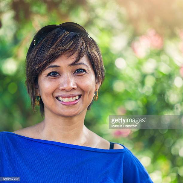 smiling woman in a garden - filipino woman stock pictures, royalty-free photos & images