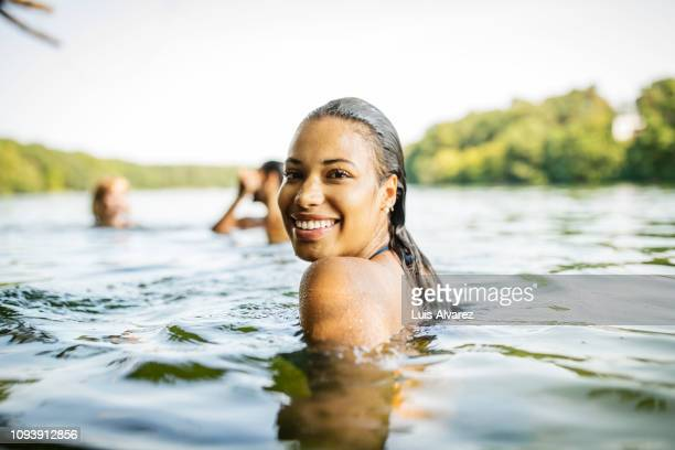 smiling woman in a lake with friends - schwimmen stock-fotos und bilder