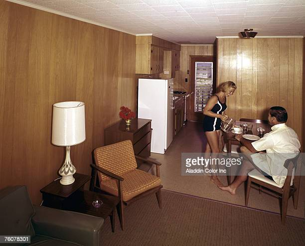 A smiling woman in a onepiece bathing suit pours a drink for a smiling man who sits at the table in the kitchenette of a woodpanelled room at an...