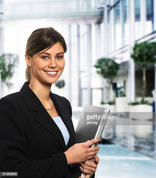 Smiling woman in a suit carrying a laptop inside a building