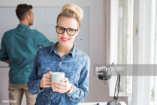 Smiling woman in an office with cup of coffee