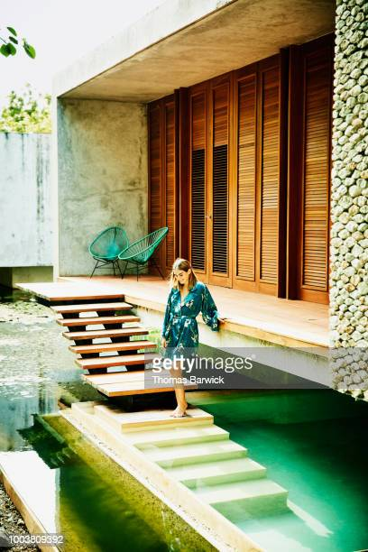 Smiling woman in bathrobe standing at edge of plunge pool outside of bungalow at luxury tropical resort