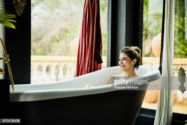 Smiling woman in bathtub in boutique hotel