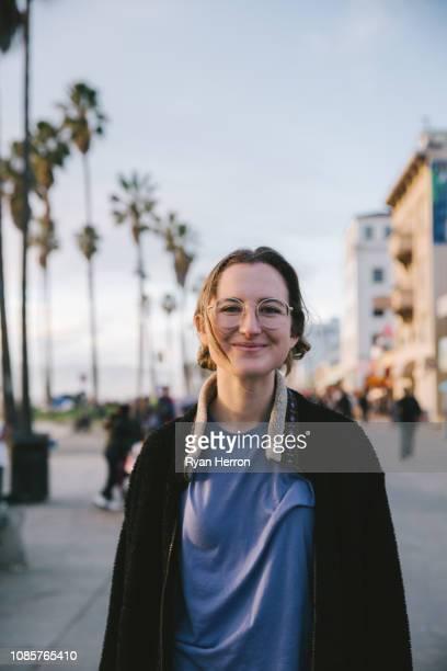 lachende vrouw in zwarte jas op strand - alleen tienermeisjes stockfoto's en -beelden