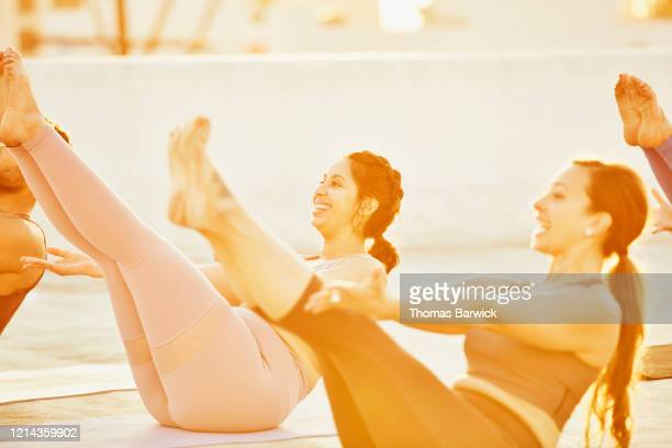Smiling woman in boat pose during rooftop yoga class