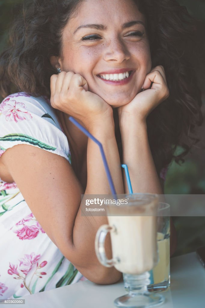 Smiling woman in cafe with hands on chin : Stock Photo