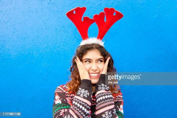 smiling woman in christmas jumper and crazy antlers - christmas jumper fotografías e imágenes de stock