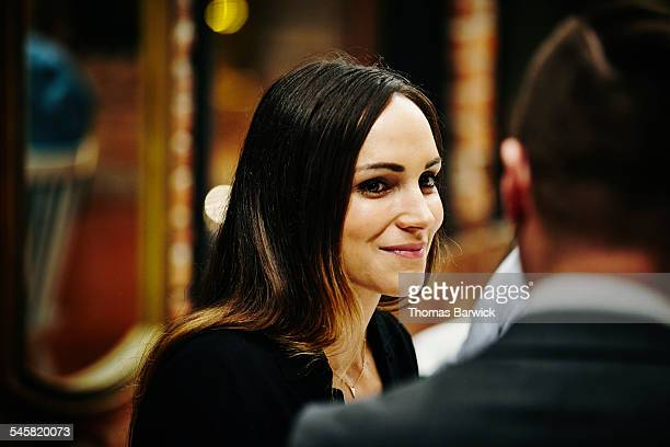 Smiling woman in conversation during dinner party