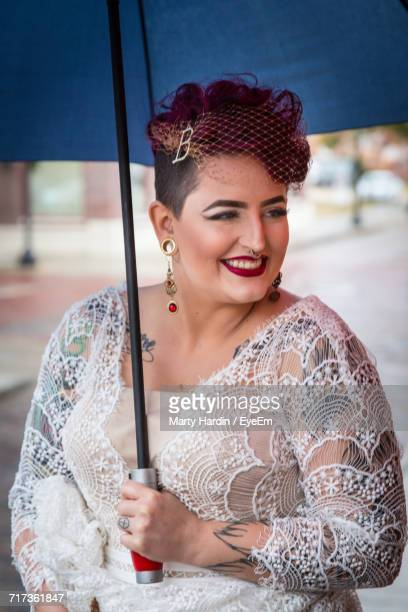 smiling woman in costume holding blue umbrella at event - marty hardin stock photos and pictures